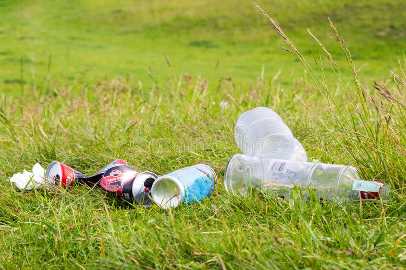 Bottles and cans in grass stock photos