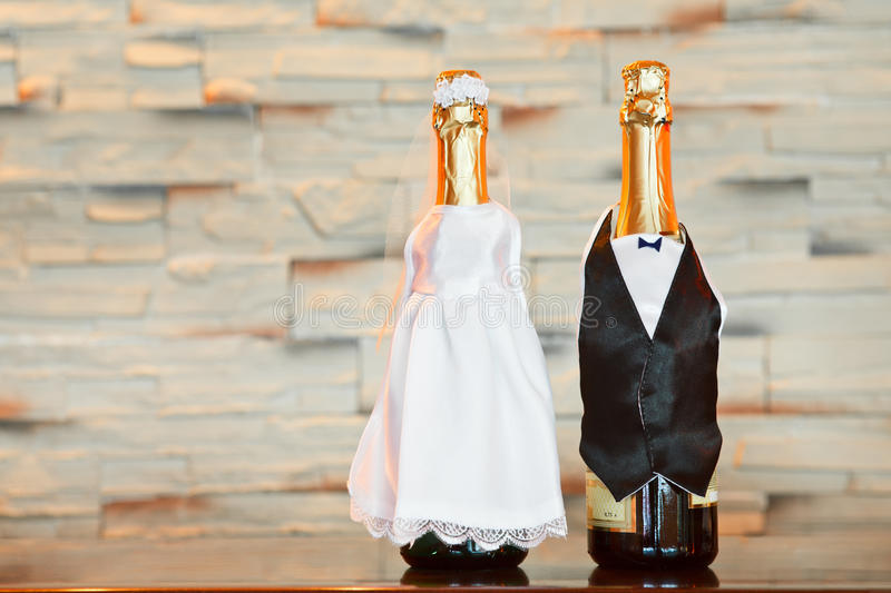 Bottles of champagne looks like bride and groom. Two bottles of champagne in bride and groom clothes in table. Copy space stock image