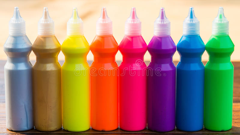 Bottles with colorful dry pigments on wooden background royalty free stock photography