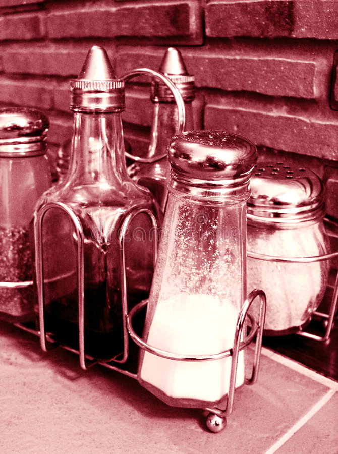 Bottles of Condiments. Image showing bottles of condiments on a metal rack, on top of a table in an italian restaurant. Condiments include salt, pepper, hot royalty free stock photos