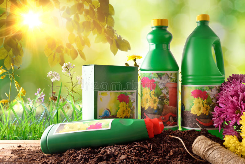 Bottles and containers of gardening products in nature with sunlight. Bottles and containers of gardening products for the growth of plants. With flowers and stock photos