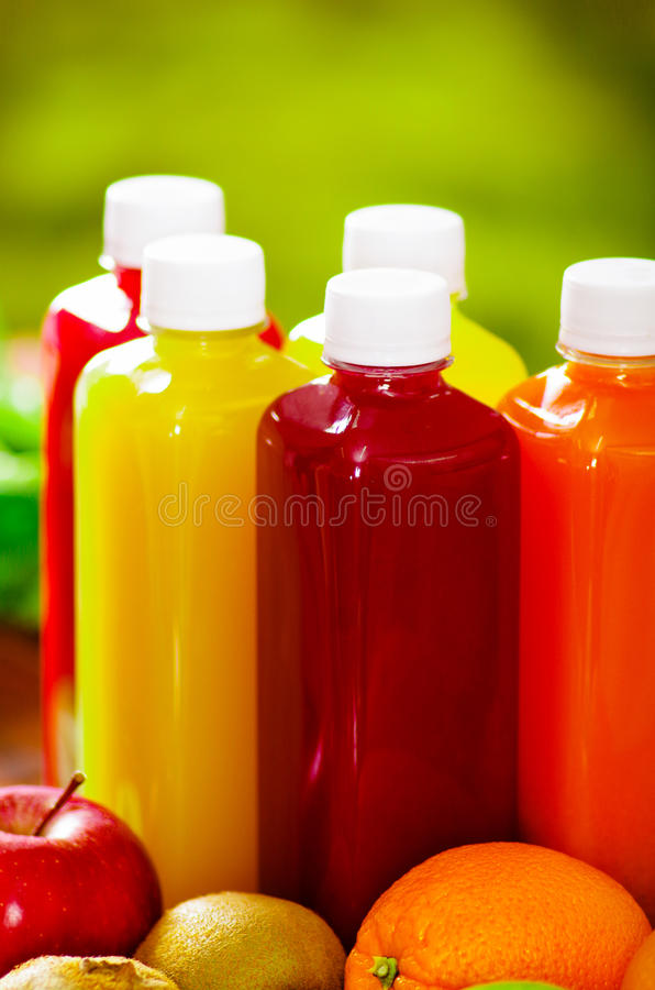 Bottles of delicious organic juice sorrounded by fruits and veggies, beautiful colors, healthy lifestyle concept royalty free stock photo