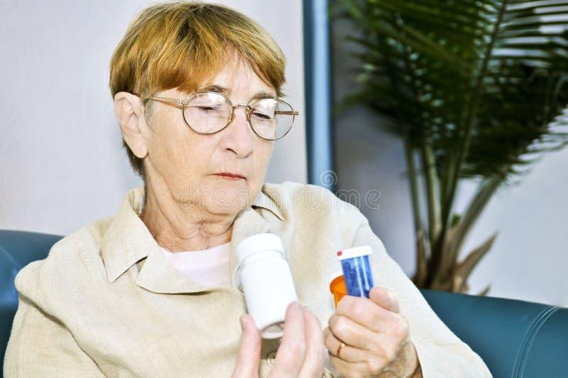 bottles den gammalare pillavläsningskvinnan royaltyfria foton