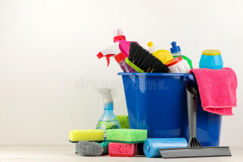 Bottles with detergent and cleaning tools in a bucket on a light background. cleaning. cleaning products. place for text. free pla royalty free stock photo