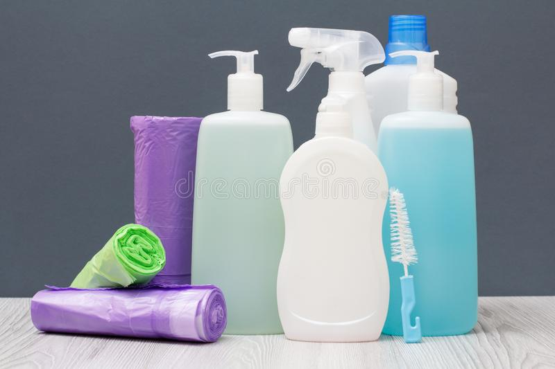 Bottles of detergent and garbage bags on gray background. Plastic bottles of dishwashing liquid, glass and tile cleaner, detergent for microwave ovens and stoves royalty free stock photos