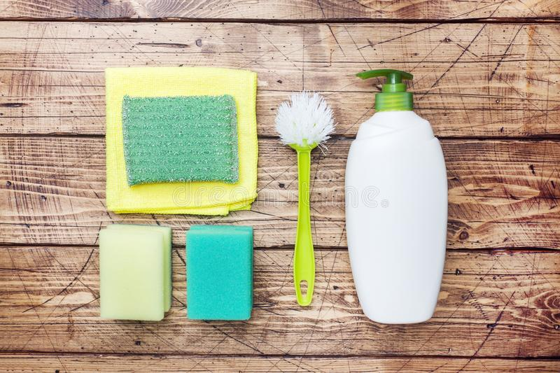 Bottles with detergents, brushes and sponges on wooden background. Colorful cleaning products. Home cleaning concept. Top view, royalty free stock images