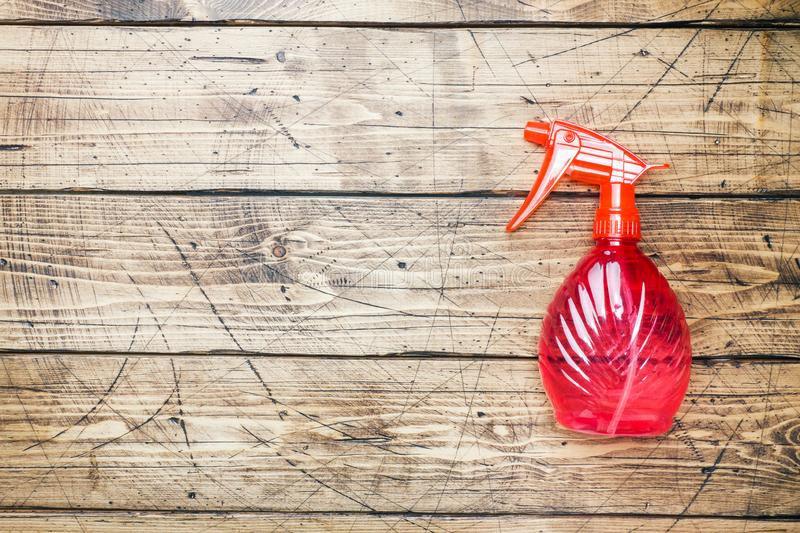 Bottles with detergents and cleaning products on wooden background. Home cleaning concept. Top view, copy space stock image