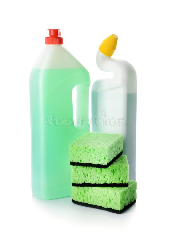 Bottles of detergents with cleaning sponges on white background stock images