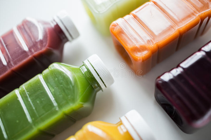 Bottles with different fruit or vegetable juices stock image