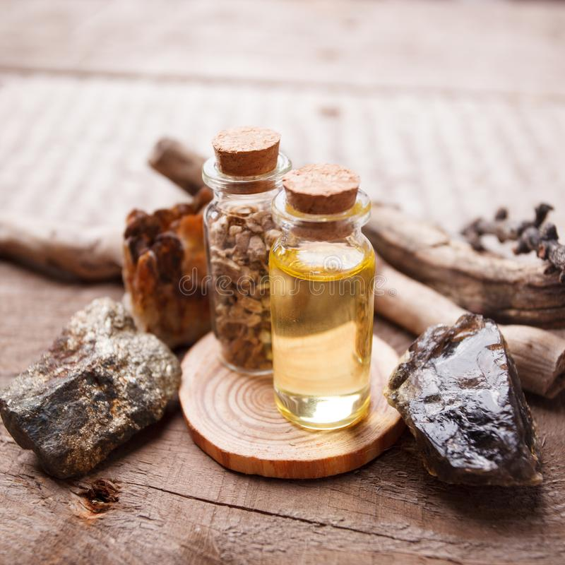 Bottles with herbs, dry flowers, stones and magic objects on witch wooden table. stock image