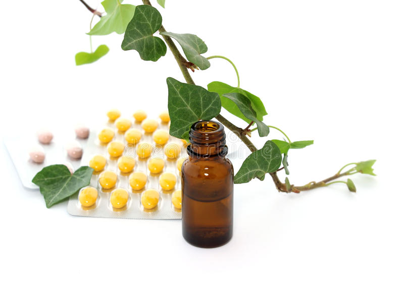 Bottles of essential oil and branch of ivy isolated stock images