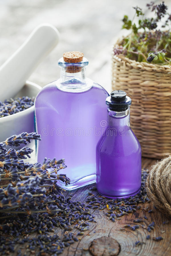 Bottles of essential oil, mortar and lavender flowers stock images