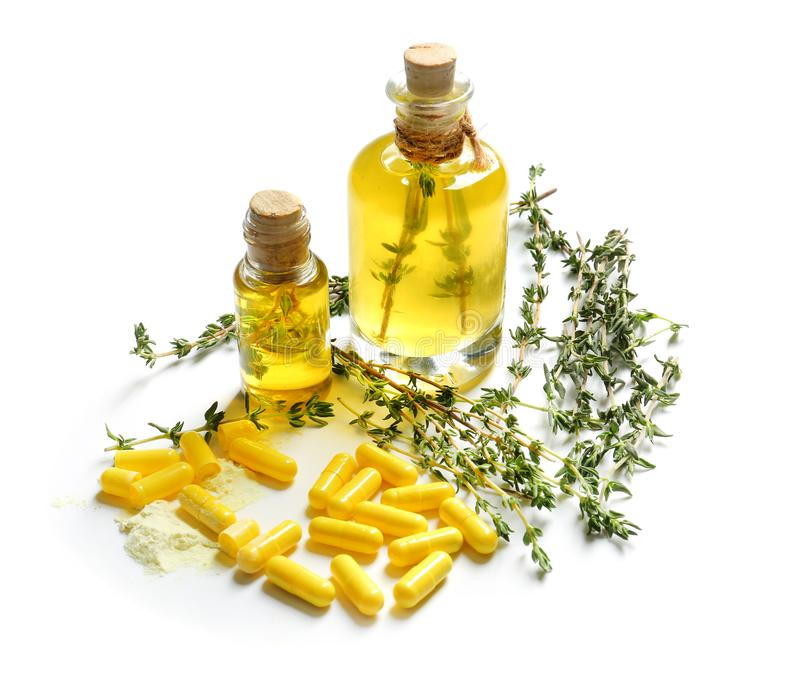 Bottles with essential oil, pills and thyme on white background stock photos