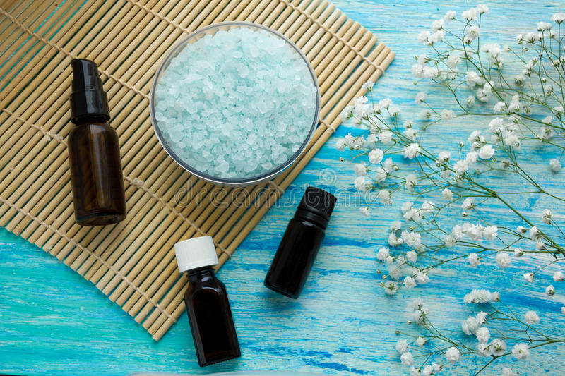 Bottles essential oil and sea salt herbal bath on wooden table, Spa with flowers royalty free stock image