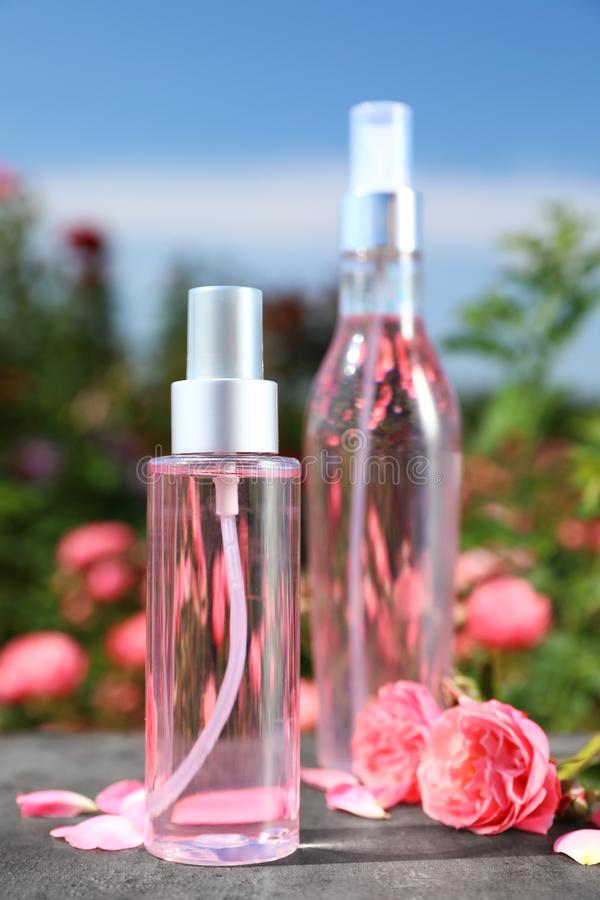 Bottles of facial toner with essential oil and fresh roses on table against blurred stock images