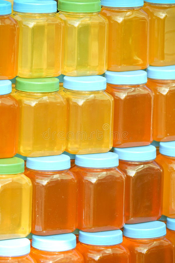 Bottles full of honey royalty free stock photography