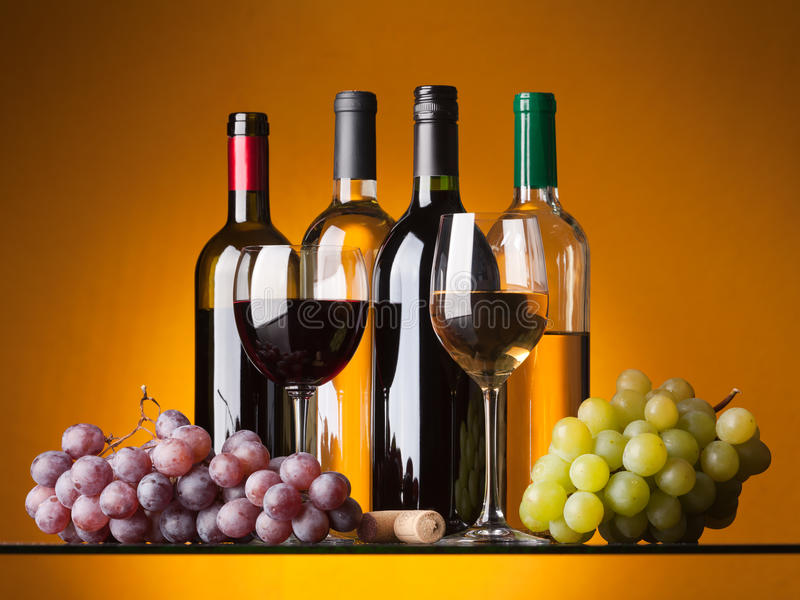 Bottles, glasses and grapes. Several bottles of white and red wine, two glasses and grapes on an orange background stock photos