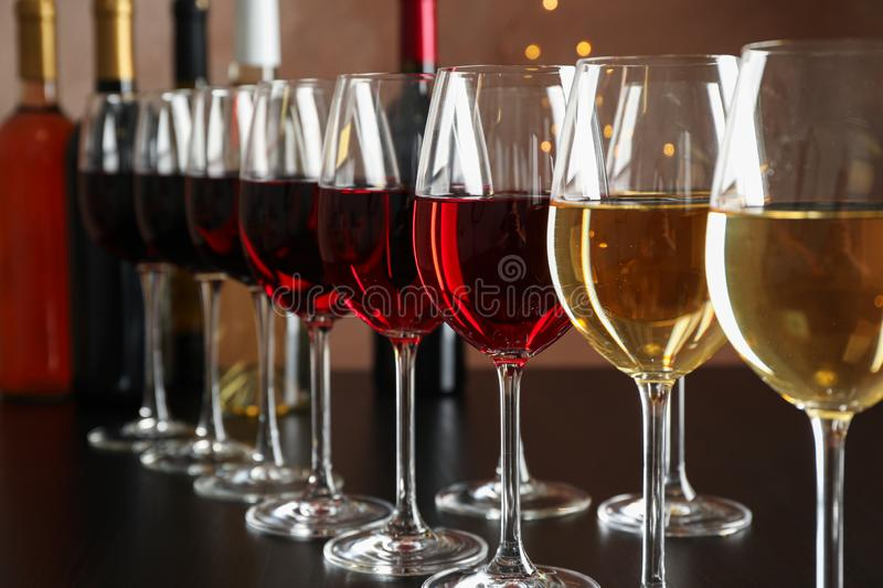 Bottles and glasses with wine on dark table, blurred lights stock photography