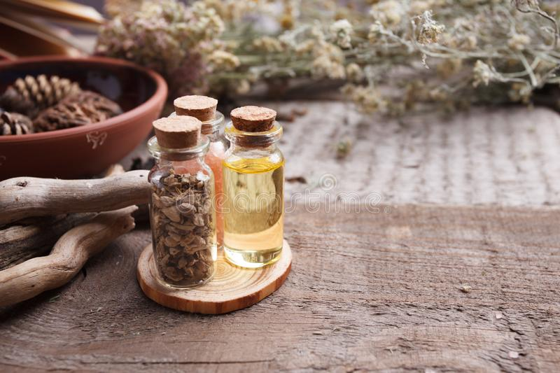 Bottles with herbs, dry flowers, stones and magic objects on witch wooden table. stock photo