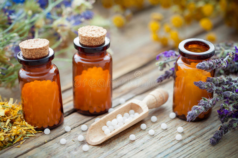 Bottles of homeopathic globules and healing herbs. Homeopathy medicine. stock image