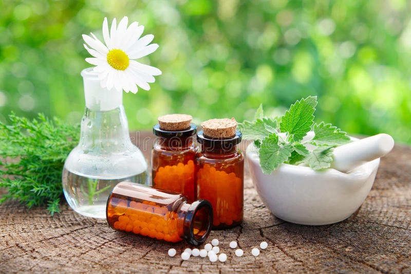 Bottles of homeopathic globules, mortar and daisy flower in flask. stock images