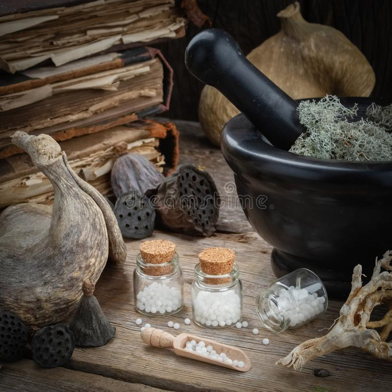 Bottles of homeopathic globules, mortar, dried moss, old books, dry roots, nuts and plants on table. stock images