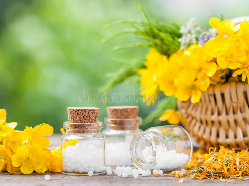 Bottles of homeopathy globules and healthy herbs. In basket royalty free stock image
