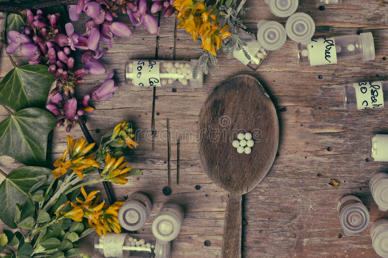 Bottles with homeopathy globules and spoon, decorated with flowe royalty free stock photos
