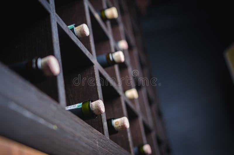 bottles hyllawine källarecognacen flankerar oaken där wine Slut upp vinflaskor royaltyfria foton