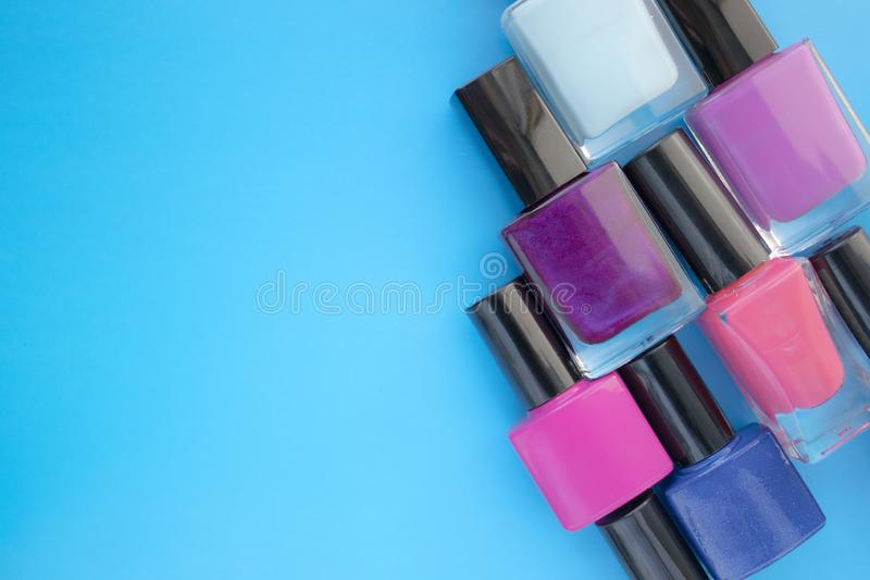 Bottles of nail polish. A group of bright manicures on a blue background. With empty space on the left stock photo