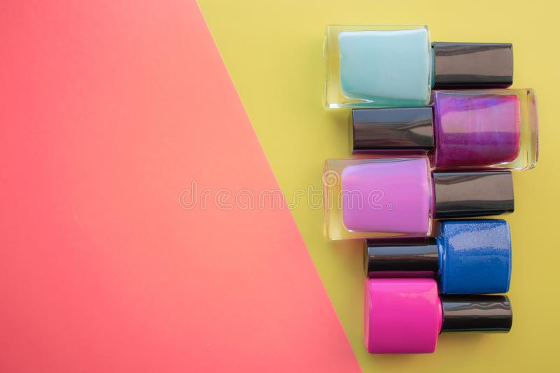 Bottles of nail polish. A group of bright manicures on a pink, yellow background. With empty space on the left stock image