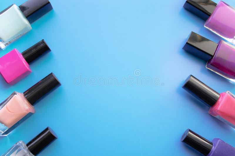 Bottles of nail polish. A group of bright nail polishes on a blue background. With empty space in the middle stock photography