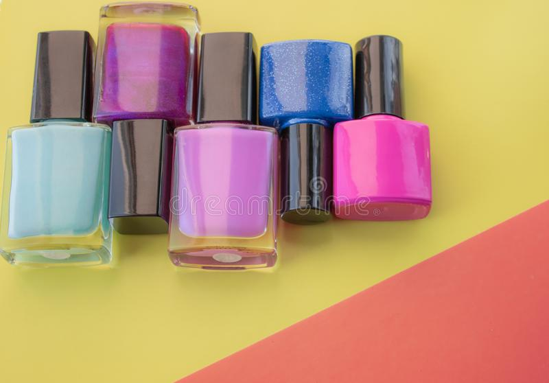 Bottles of nail polish. A group of bright nail polishes on a colored, yellow background royalty free stock photography