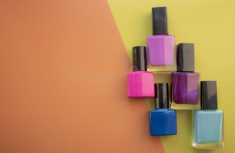 Bottles of nail polish. A group of bright nail polishes on a colored, yellow background. With empty space on the left royalty free stock photography