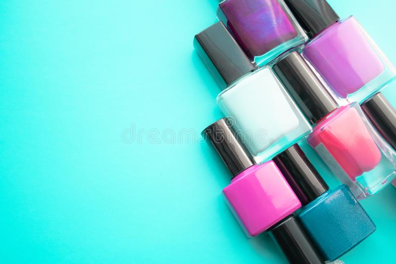 Bottles of nail polish. A group of bright nail polishes on a green background. With empty space on the left stock photos