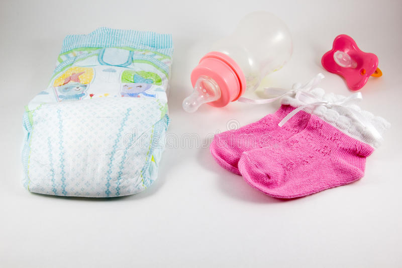 Bottles, pacifiers, and baby diaper on a white background royalty free stock photography