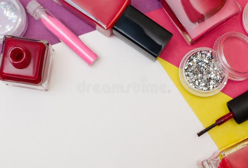 Bottles of red nail polish and nail art glitter. royalty free stock photos