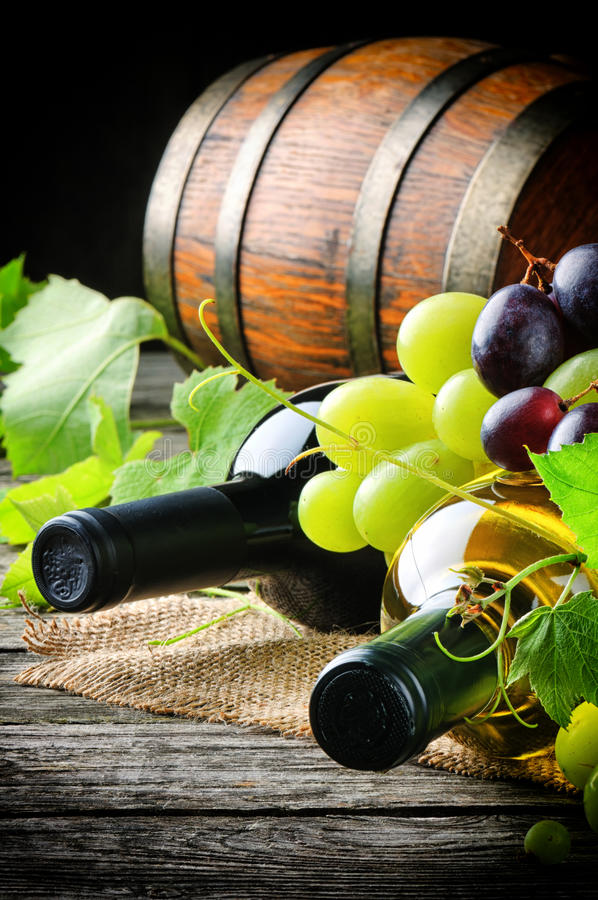 Bottles of red and white wine with fresh grape royalty free stock photo