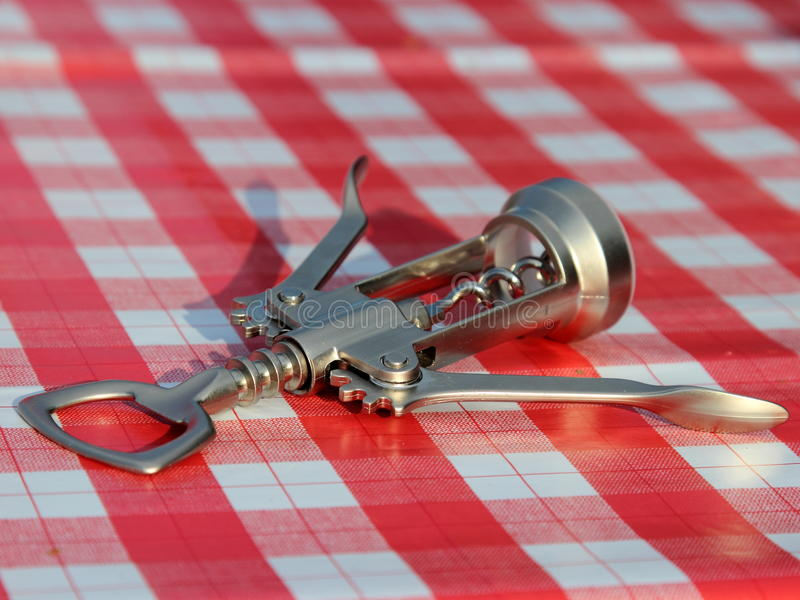 Bottles stopper opener. Bottle opener on table covered with red tablecloth stock photo