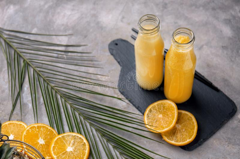 Bottles of tasty yellow smoothie with fruits and tropical leaf on grey table royalty free stock images