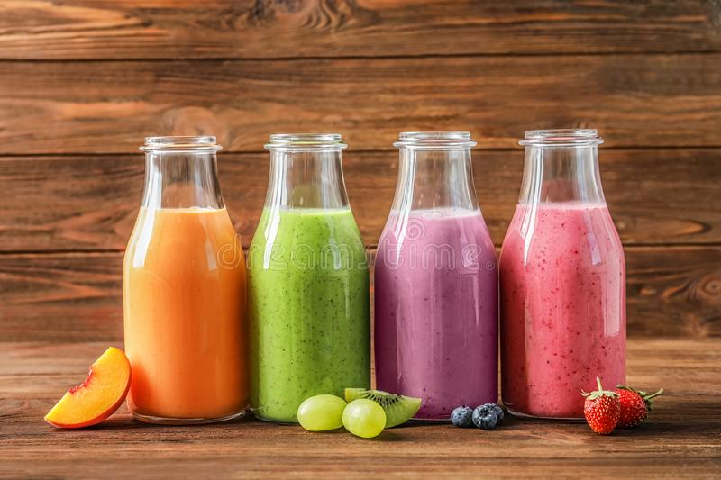 Bottles with yummy smoothie on background royalty free stock images