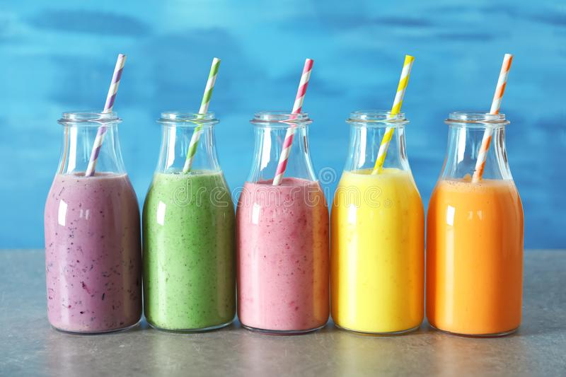 Bottles with yummy smoothie on table against background royalty free stock photos