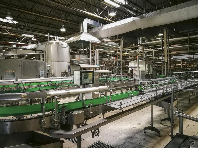 Bottling automated line inside a brewery. Modern bottling line and auxiliary installations inside a brewery , on the conveyor belts beer bottles follow the stock image