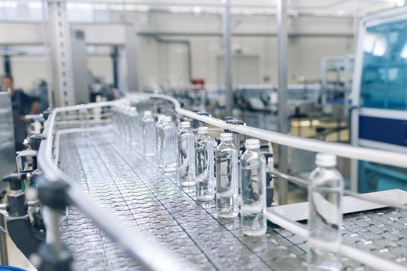 Water bottling factory. Bottling plant - Water bottling line for processing and bottling pure mineral carbonated water into bottles royalty free stock image