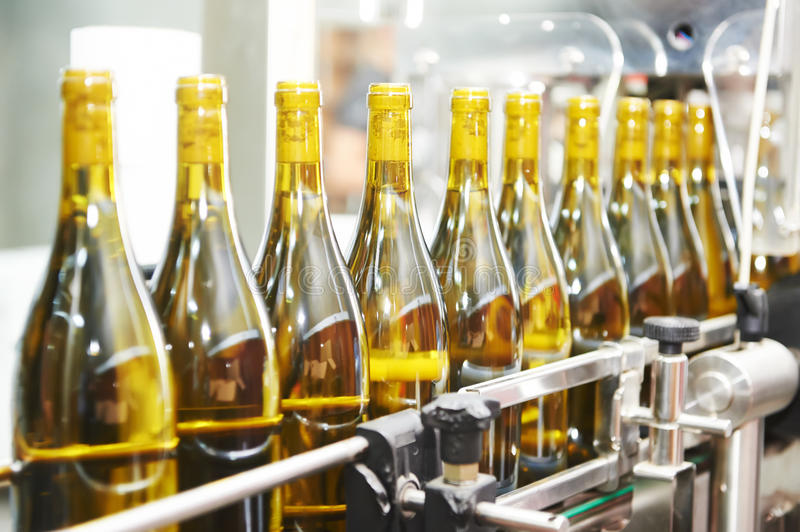 Bottling and seaaling conveyor line at winery factory. Bottles with wine on bottling and sealing conveyer production line at modern winery factory. Shallow DOF stock photos