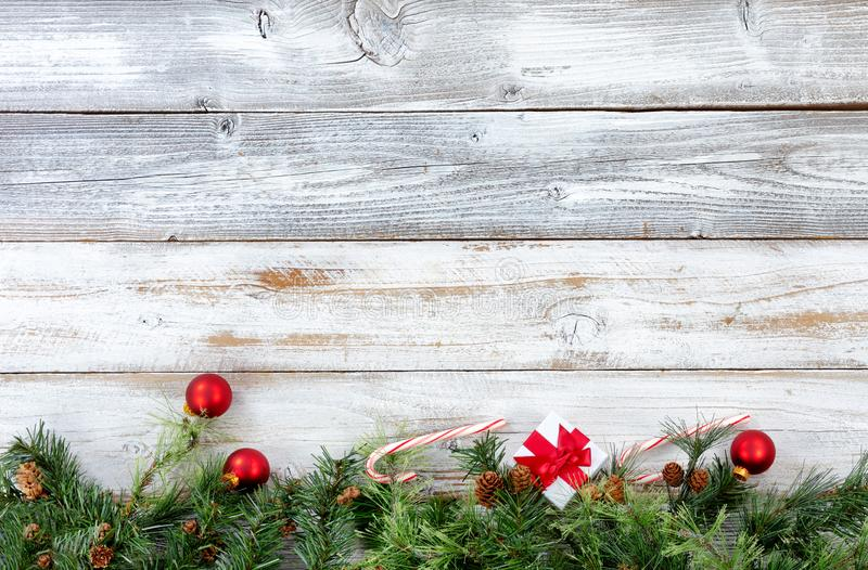 Bottom border of Christmas evergreen branches with other holiday. Decorations on white rustic wooden boards stock photos