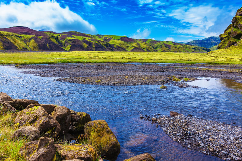 On bottom of canyon streams flow. On bottom of canyon many streams flow. Canyon Pakgil in Iceland. Picturesque basalt hills overgrown green grass and moss stock image
