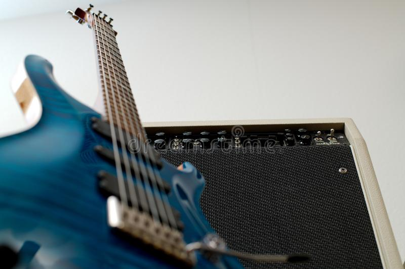 Bottom of the guitar and amp. Bottom of guitar and amplifier. Ready to rock and roll. Deep turquoise and black contrast perfectly royalty free stock photos