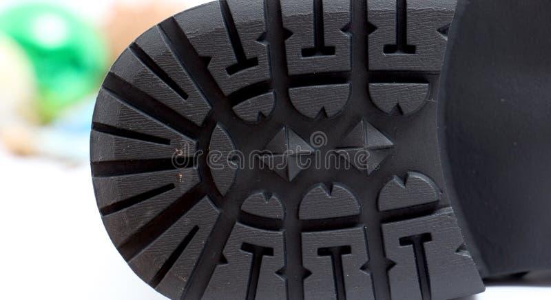 Bottom of a men`s black winter boot, patterns and texture. Picture of a Bottom of a men`s black winter boot, patterns and texture royalty free stock image