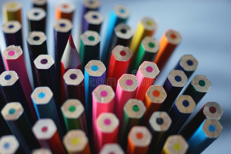 Bottom of multicolored wooden crayons and one sharp color pencil stock photo